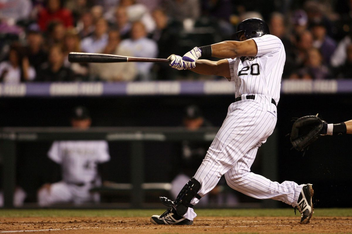April 17, 2012; Denver, CO, USA; Colorado Rockies catcher Wilin Rosario (20) hits an RBI double during the fourth inning against the San Diego Padres  at Coors Field.  Mandatory Credit: Chris Humphreys-US PRESSWIRE