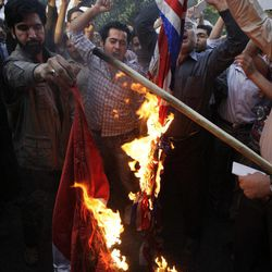 Iranian protestors burn a British and a French flag in front of the French Embassy during a demonstration to condemn a French magazine caricaturing prophet Muhammad in Tehran, Iran, Sunday, Sept. 23, 2012.