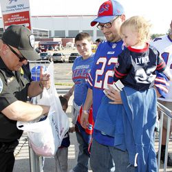 Aug 16, 2013; Orchard Park, NY, USA; Erie County sheriff deputy Mike Monile checks the diaper bag of Lisa Chaplin and Scott Chaplin of Randolph , NY before entering the stadium before the game between the Buffalo Bills and the Minnesota Vikings at Ralph W