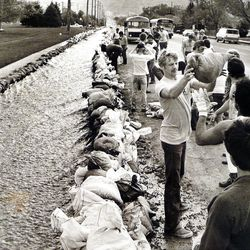 Young first time offenders from correction facility heft sandbags along Sunnyside Avenue. May 16, 1984.
