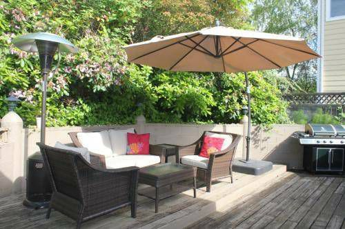 A wood patio with a barbecue, seating, and a large umbrella-style shade.