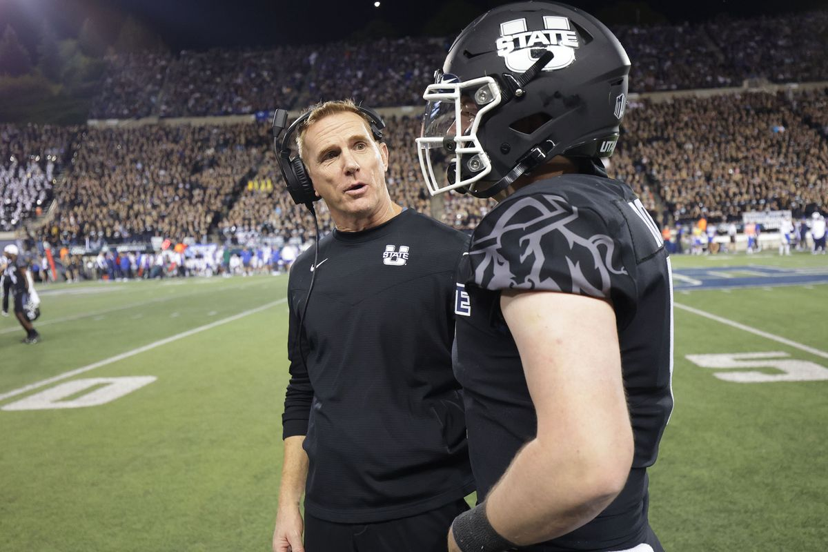 Utah State Aggies head coach Blake Anderson talks with Utah State Aggies quarterback Logan Bonner.