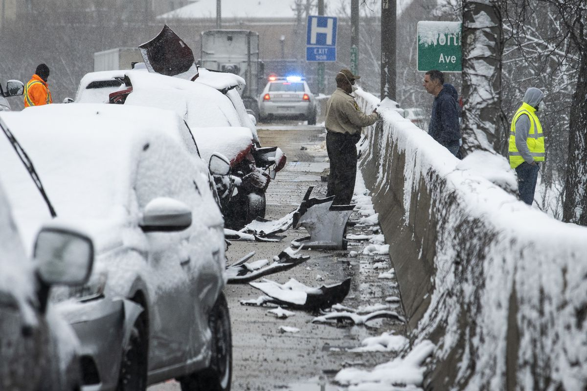 An Illinois State Police trooper investigates the scene of a massive pileup crash involving nearly 60 vehicles, sending more than a dozen people to hospitals, in the inbound lanes of the Kennedy Expressway near North Avenue, Wednesday morning, April 15, 2020.