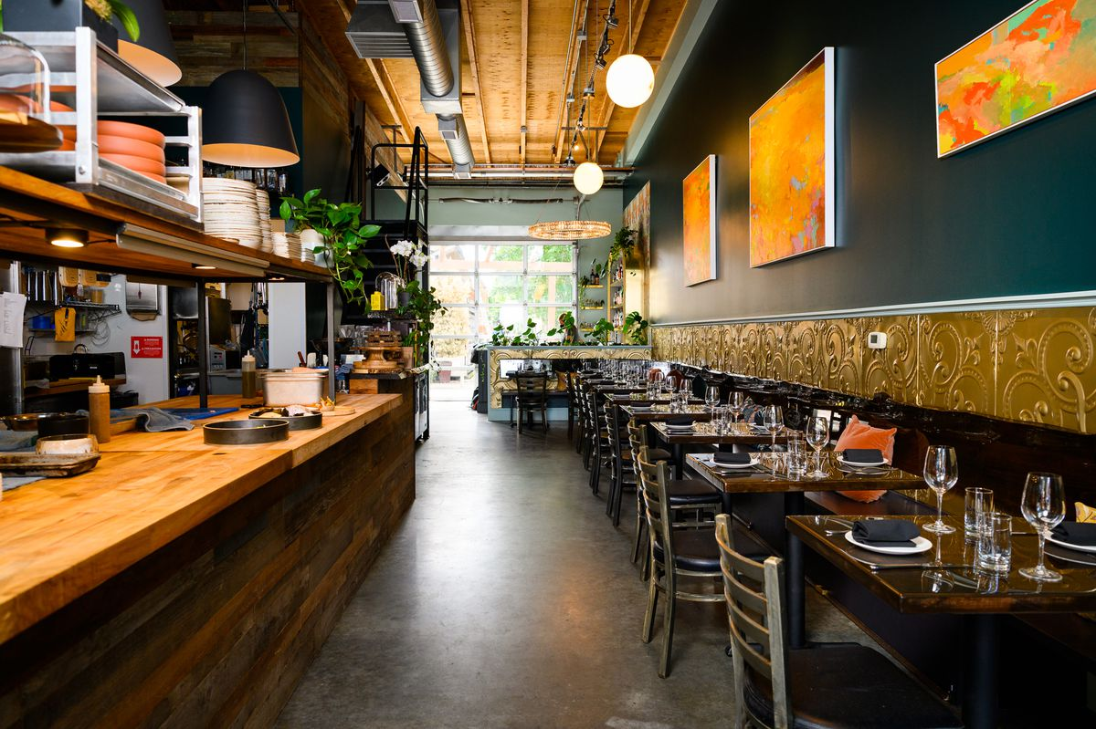 A long dining room with tables along one wall, a concrete floor, and a wooden kitchen bar