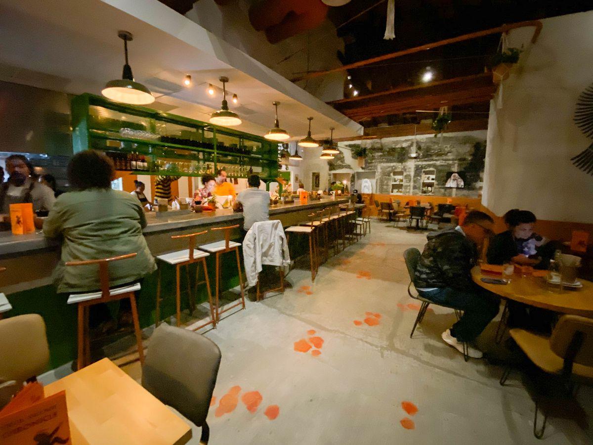 A long open bar inside a dinnertime restaurant with cement touches.