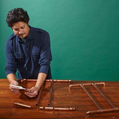 Man Glues Base And Top Frames Of Copper Log Holder