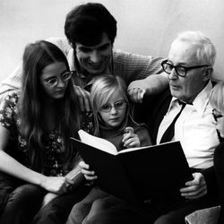Kresimir Cosic looks at a book with a family.