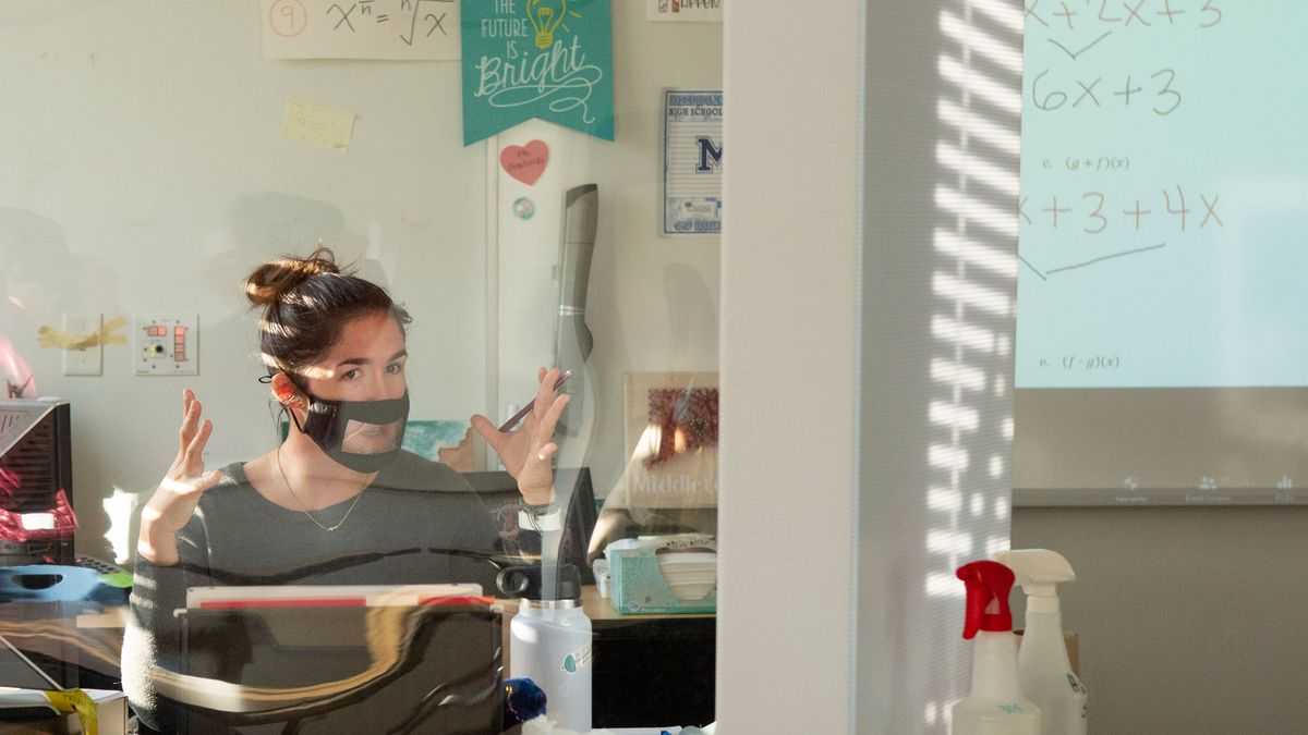 A math teacher wearing a mask sits behind her desk, which is protected by a large glass shield due to COVID-19 procedures.