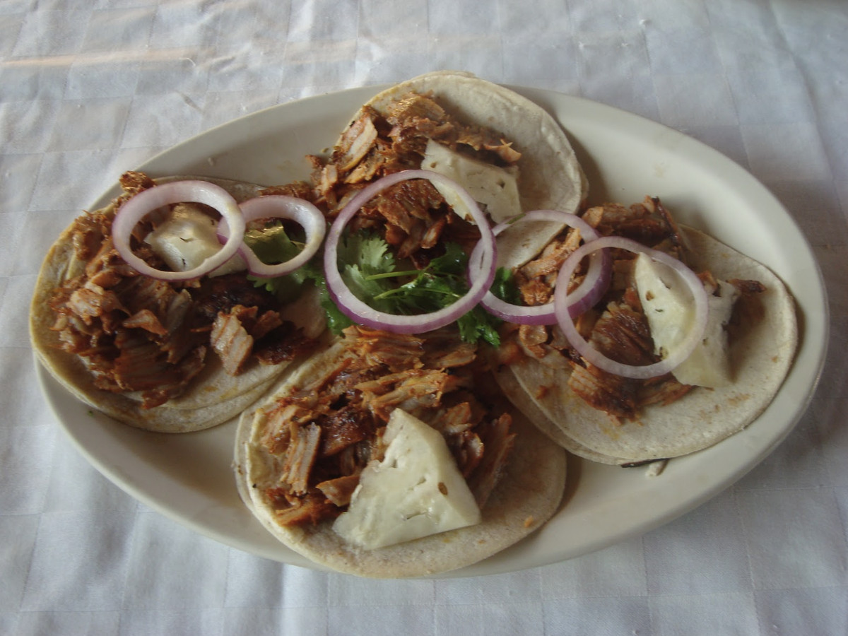 Four tacos on a plate topped with onion rounds.