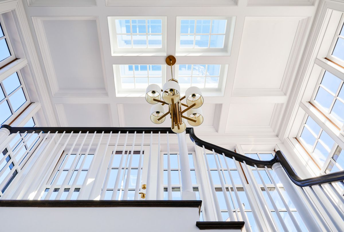 A worm's eye view photo of a grand staircase and skylights. The staircase, walls, windows and ceiling are all white and the banister is a dark, rich brown color. There is a pendant light hanging in the middle of the ceiling, along the cross section of four sky light windows.