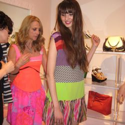 Nanette redoes the model's incorrectly tied belt.