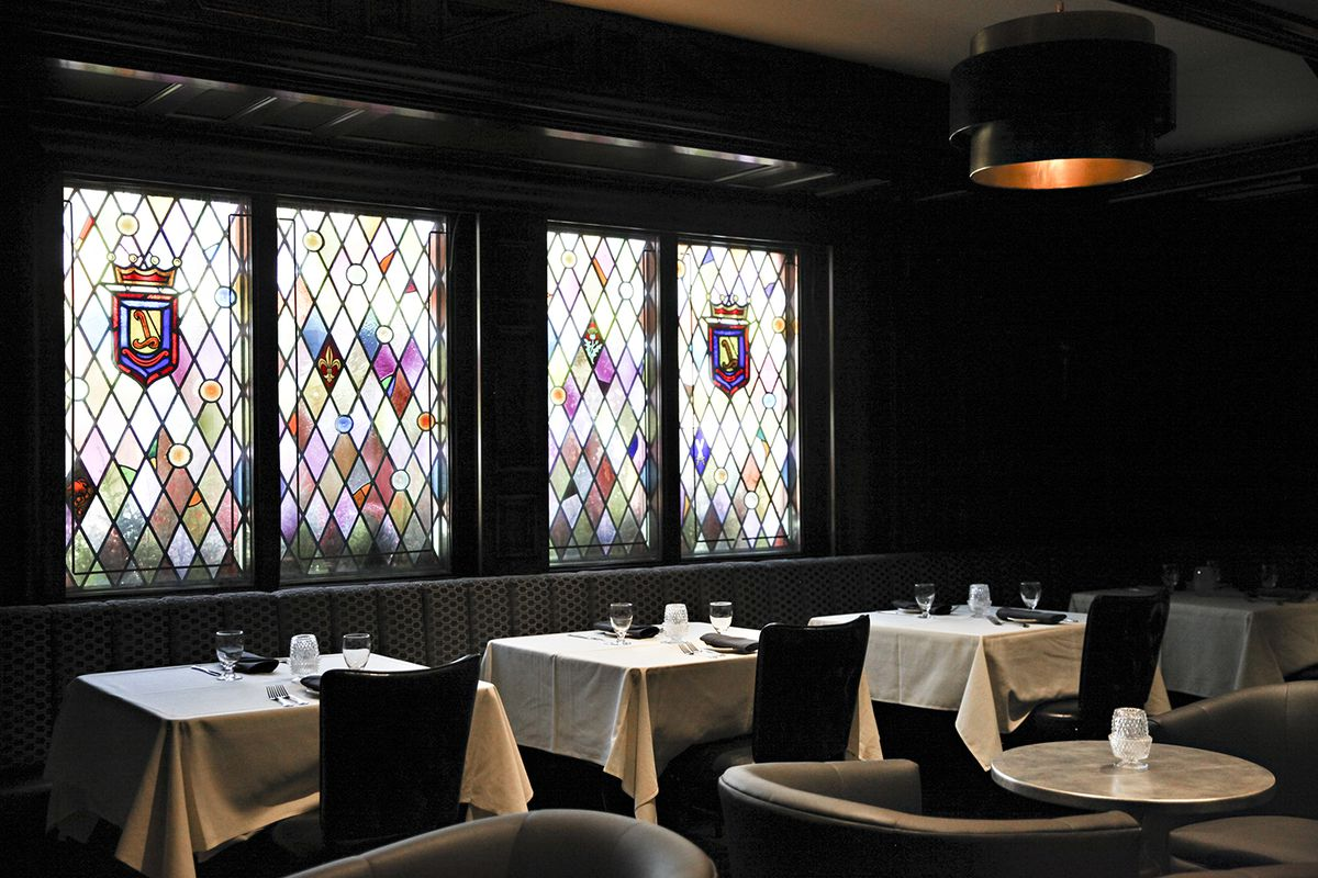 Stained glass windows behind a dining room, set with white tablecloths.