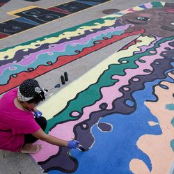 Liz Lambson puts the final touches on one of two letters that she painted as part of a Black Lives Matter mural outside of the City-County Building in Salt Lake City on Tuesday, Aug. 4, 2020.