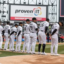 Players on the field stand for an In Memoriam video. | Erin Brown/Sun-Times