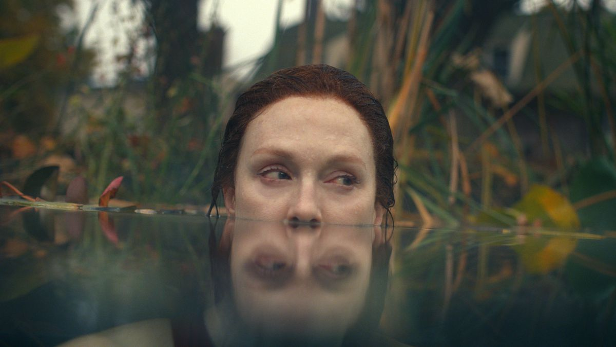 Julianne Moore, submerged in water up to her nostrils, in front of a wild jungle background in Lisey's Story