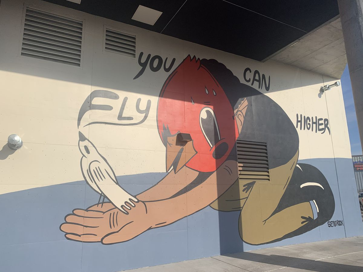 """One section of the 240-by-24-feet mural features a kneeling figure wearing a mask and holding a white bird, bearing the message, """"You can fly higher."""""""