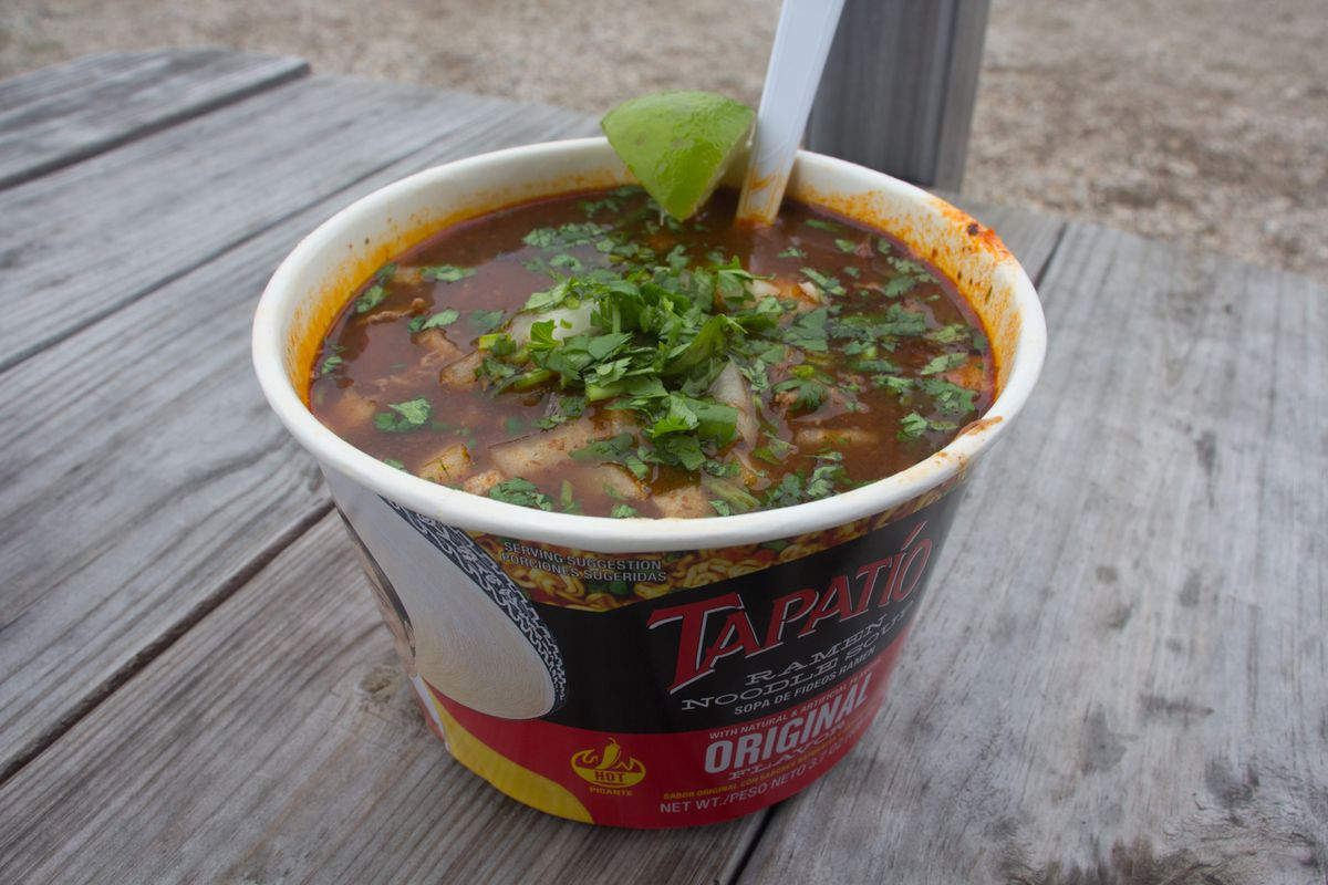 A large cup of Tapatío ramen with visible consomme, diced onions, and cilantro, with a lime slice tucked onto the rim, and a plastic fork in the bowl, all placed on a wooden table outside