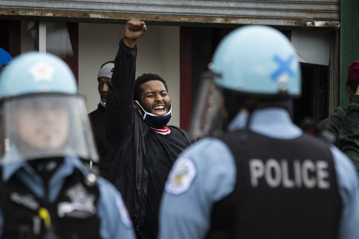 Chicago police officers clash with hundreds of protesters Monday outside a store that had been looted near East 71st Street and South Chappel Avenue in South Shore.