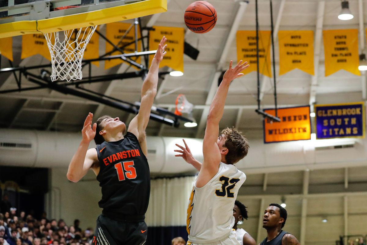 Evanston's Blake Peters (15) jumps up to block a shot by Glenbrook South's Dom Martinelli (32).