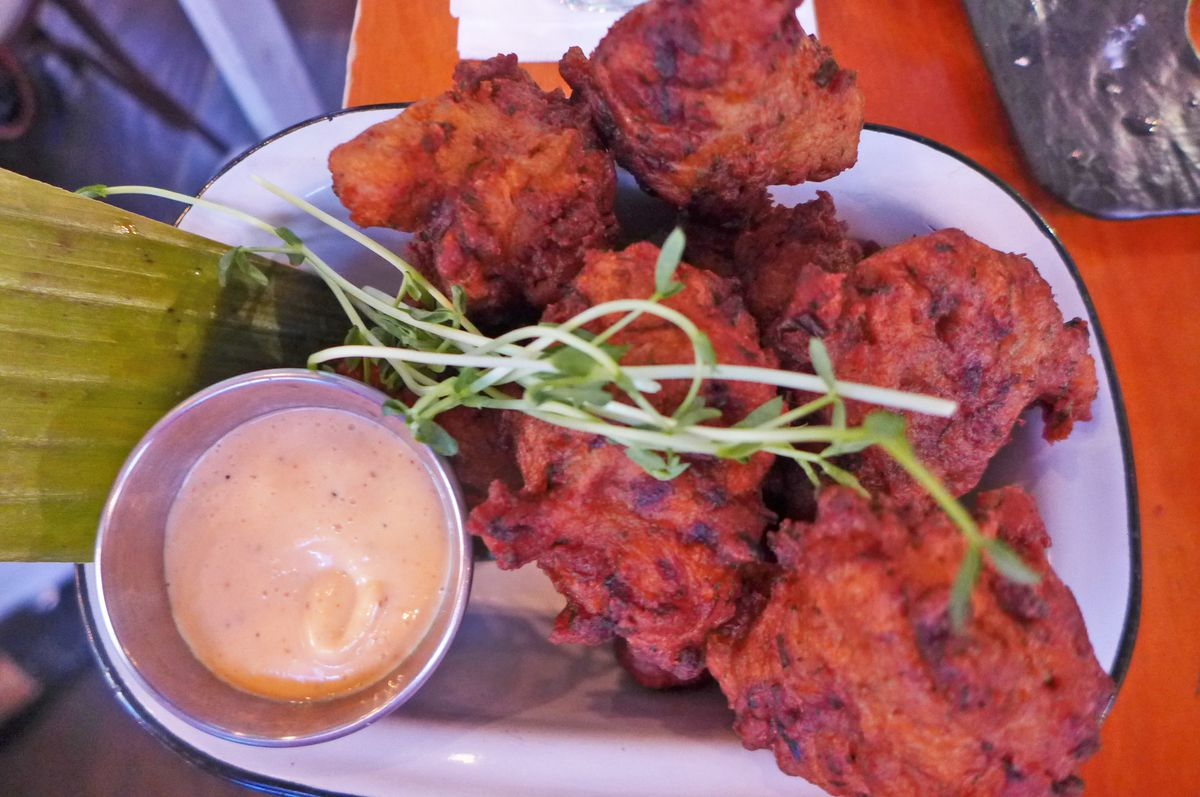 A bunch of bright red fritters on a banana leaf with pink sauce on the side.