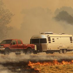 Cars turn around on I-84 as fire burns along the freeway near Weber Canyon on Tuesday, Sept. 5, 2017.