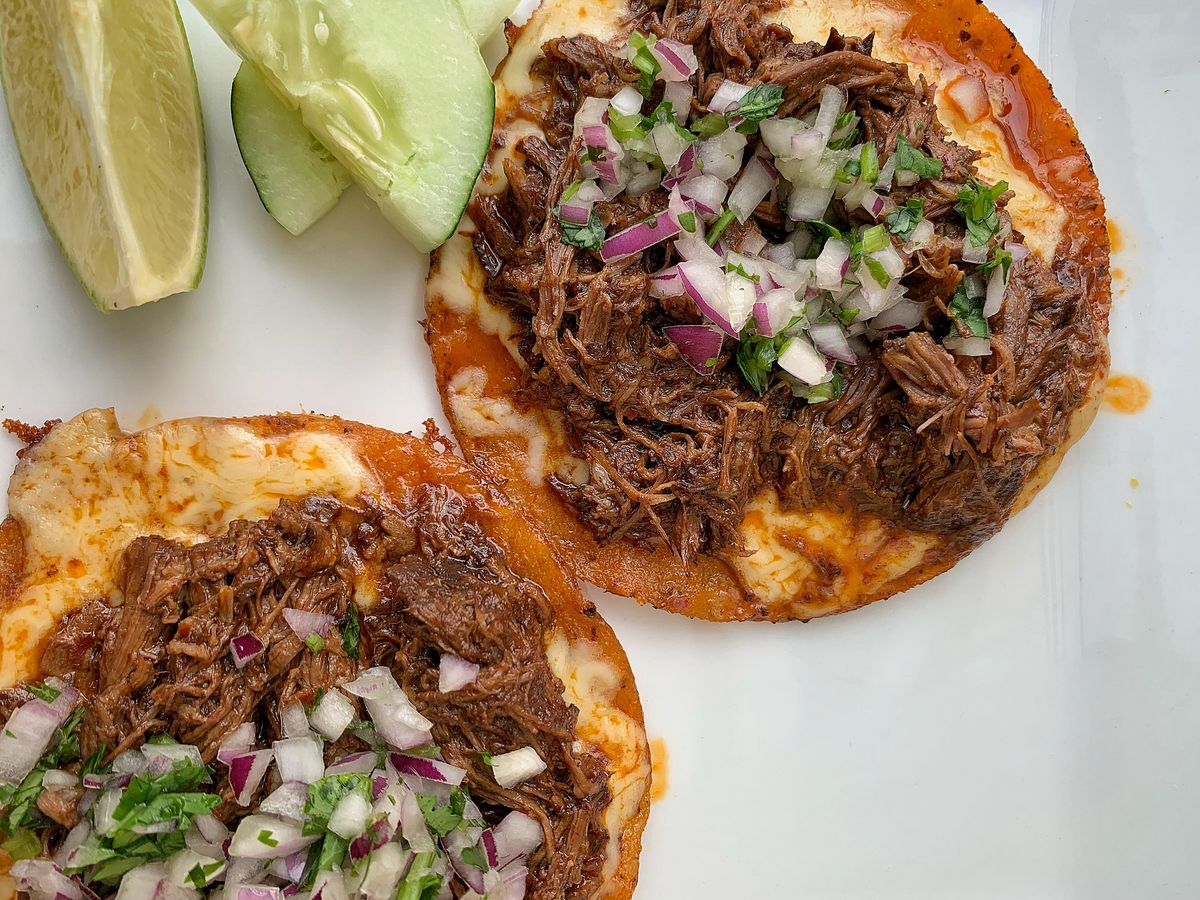 Closeup of two meaty birria tacos, garnished with red onion, cilantro, and lime