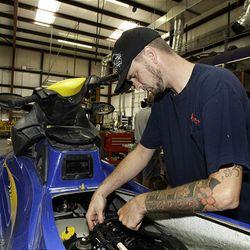 Jeremy Lavine working to repair a jetski  in Tampa, Fla.