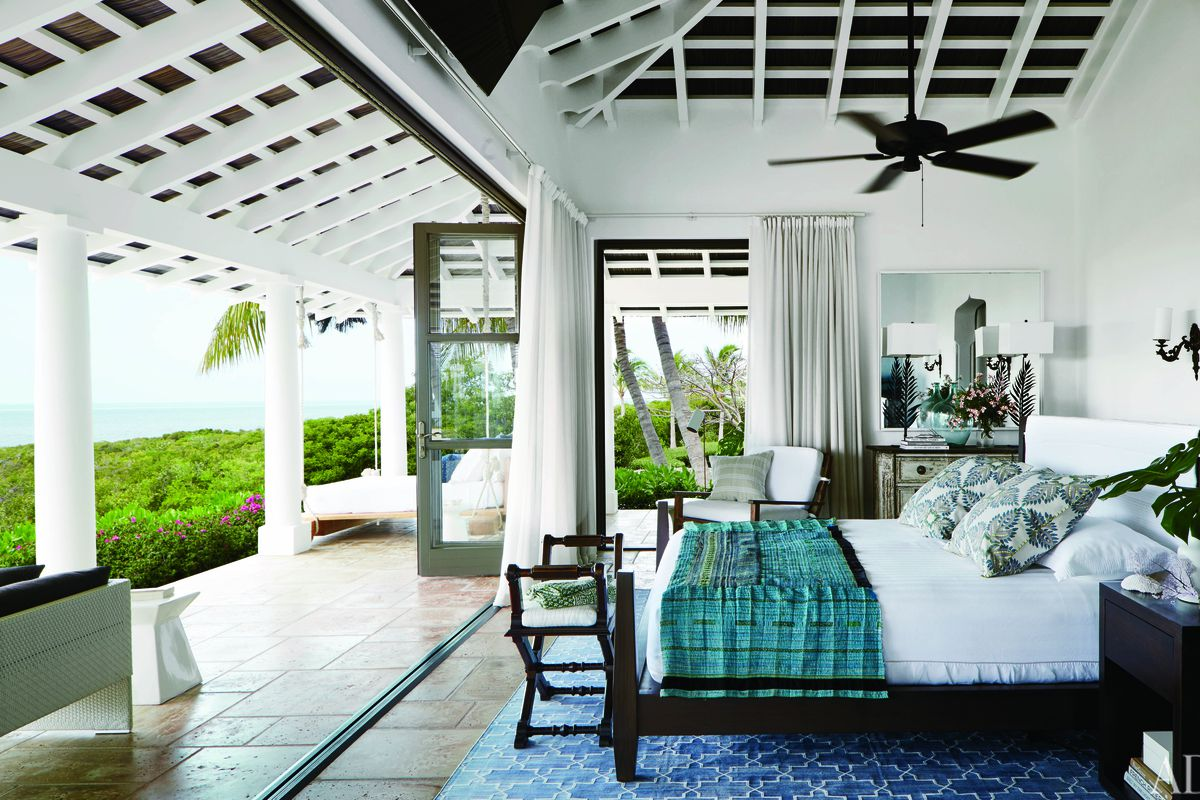 Interior shot of white bedroom that opens up to the ocean.