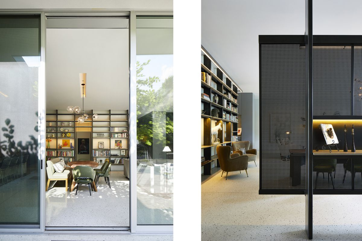 Floor-to-ceiling sliding glass doors open the living area to the garden. A black metal screen delineates the entry.