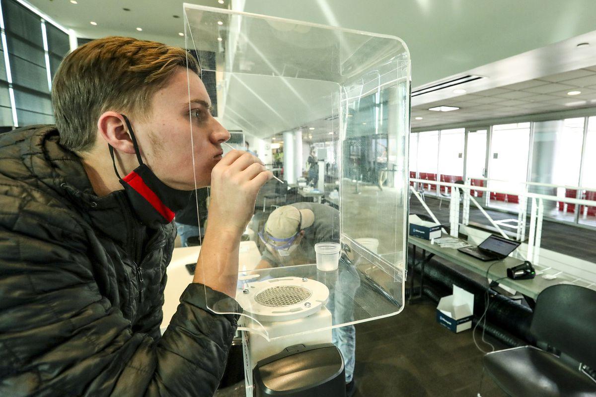 University of Utah freshman Daniel Wray swabs his nostril as he takes a rapid COVID-19 test at Rice-Eccles Stadium in 2020.