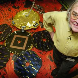 Planetary scientist Colin Pillinger stands next to a scale model of the Beagle 2 lander.