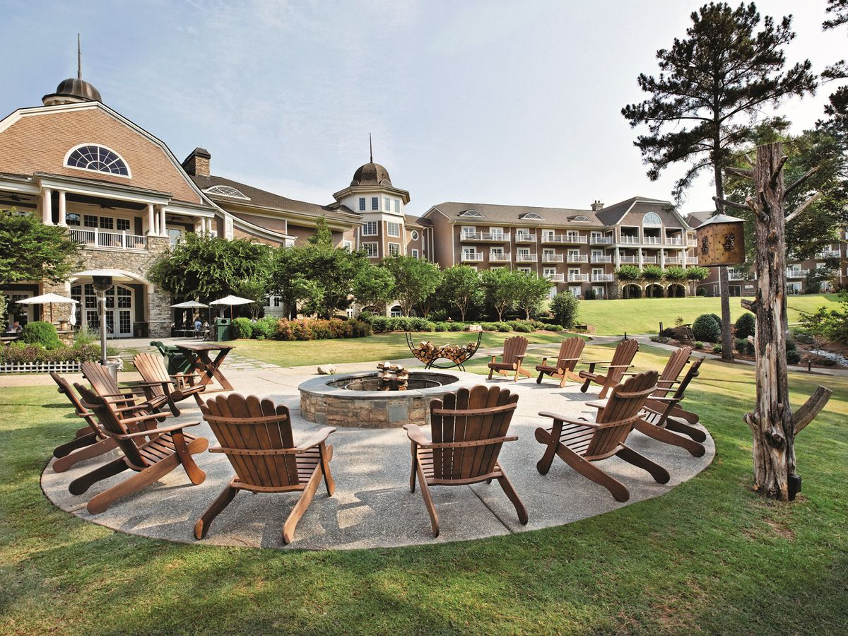 Chairs surrounding fire pit with hotel in background.