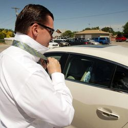 Former state Sen. Dan Liljenquist puts on a tie prior to speaking to pastors at the Salt Lake Christian Center in Salt Lake City  Tuesday, June 12, 2012.