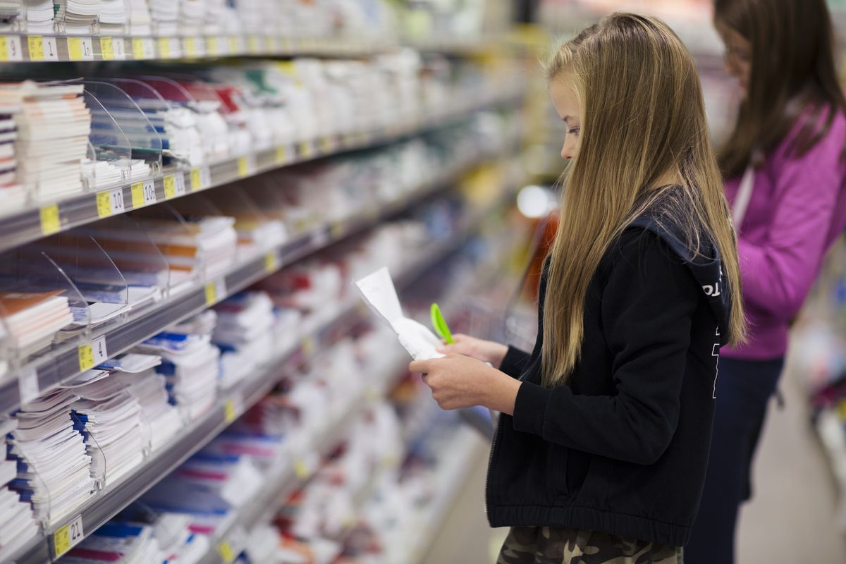 A young girl surveys her back-to-school supply list in a big box store aisle.
