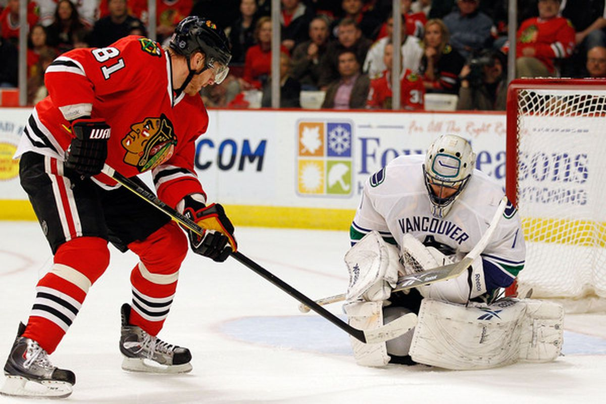 Roberto Luongo showing off his ability to hold onto the puck. while Marian Hossa stares and tries to will the puck loose.