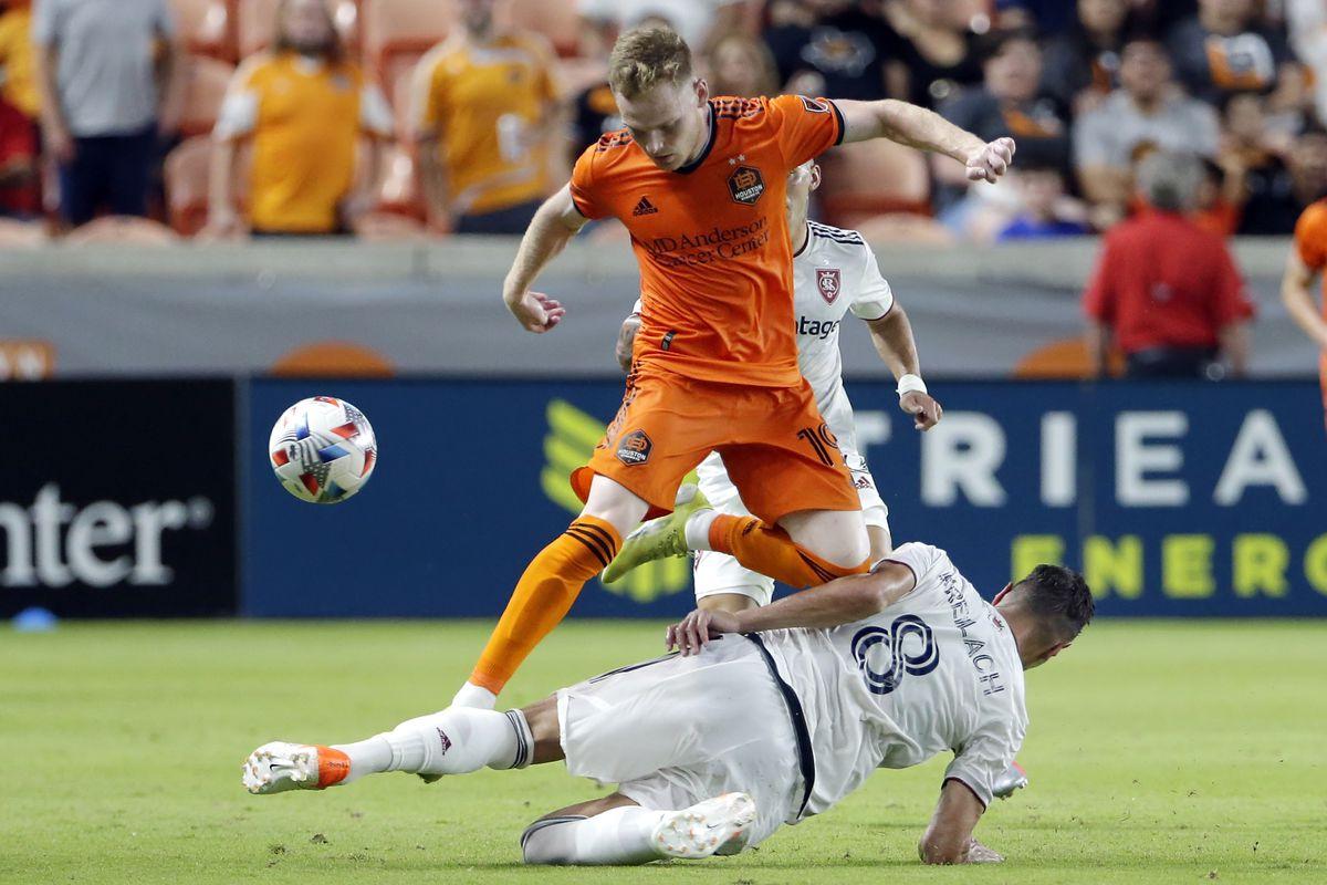 Houston Dynamo forward Tyler Pasher (19) goes over Real Salt Lake midfielder Damir Kreilach, July 31, 2021, in Houston.