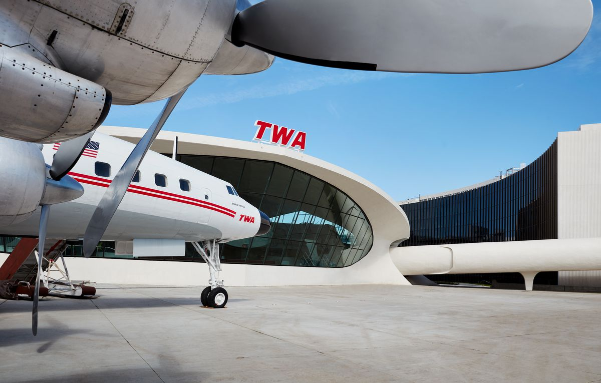 A white and red plane sits on a tarmac.