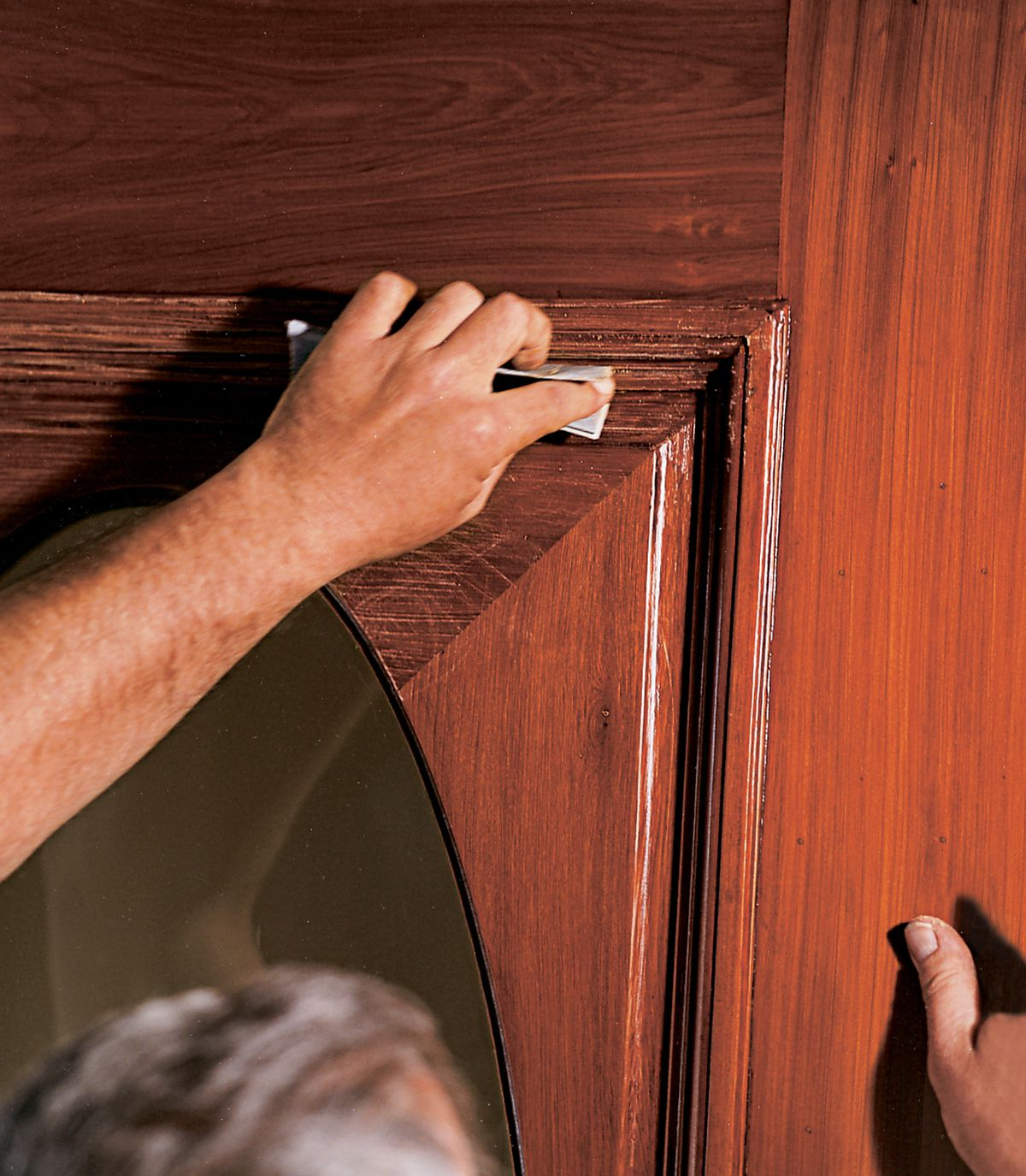 Man Applies Final Finishing Coat On Door And Then Attaches Hardware