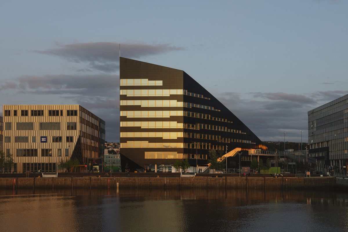 Dark angular building on a waterfront features stripes of glazing glowing during dusk.