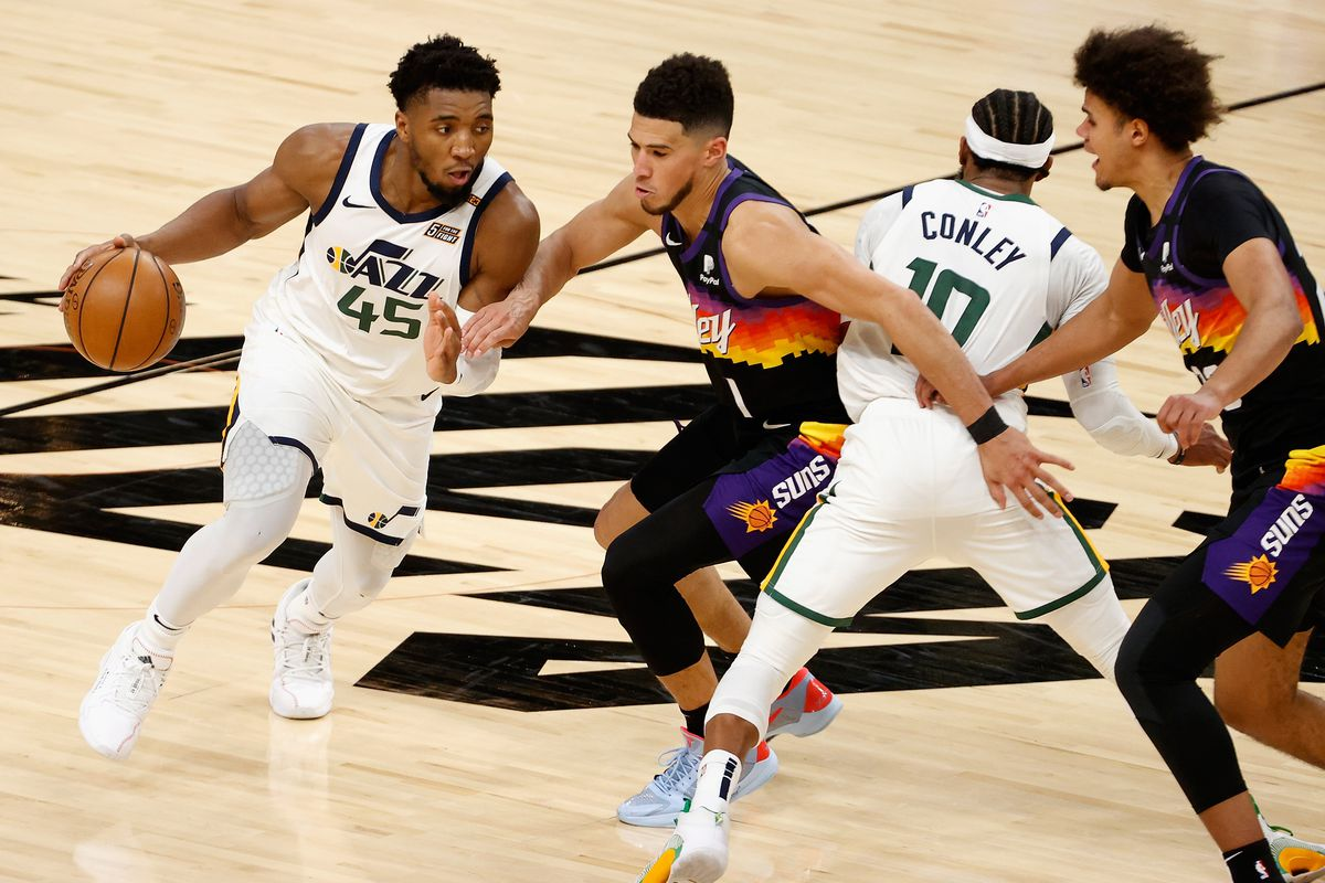 Donovan Mitchell of the Utah Jazz drives the ball against Devin Booker of the Phoenix Suns during the overtime of the NBA game at Phoenix Suns Arena on April 07, 2021 in Phoenix, Arizona. The Suns defeated the Jazz 117-113 in overtime.