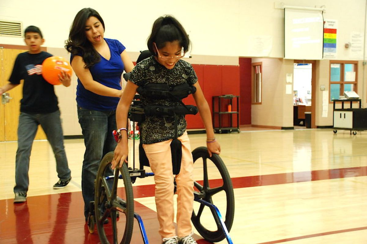 Gabi, a student at Denver's Bruce Randolph School, works with a paraprofessional during an adapted physical education class in 2015.