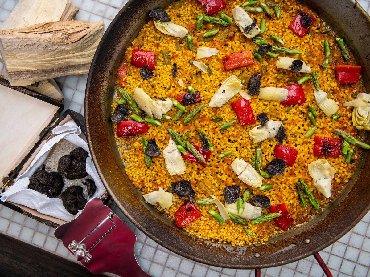 Vegan paella gets cooked over orange wood fire at Xiquet