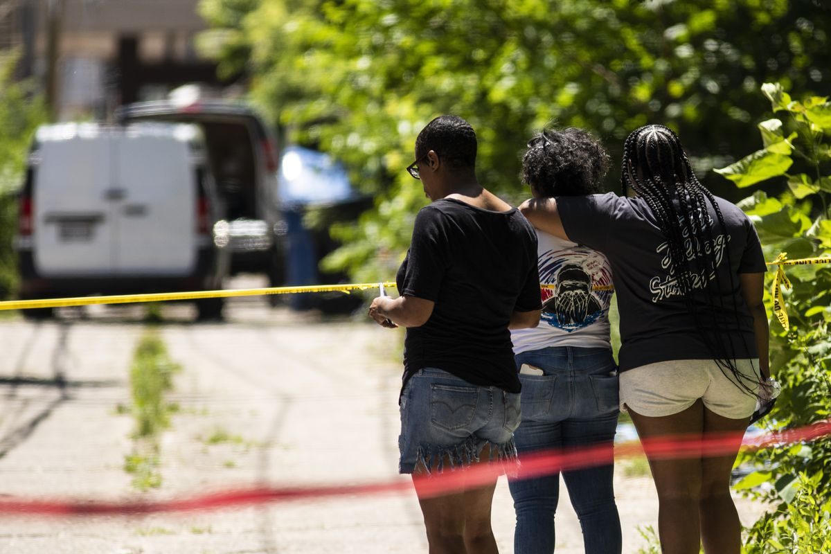 People watch as a crew removes four bodies from a house in the 6200 block of South Morgan after they were all shot to death when an argument broke inside the Englewood building, Tuesday afternoon, June 15, 2021. Four other people were wounded in the shooting.