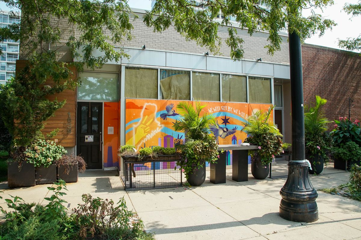 The exterior of a colorful restaurant taken from across the street.