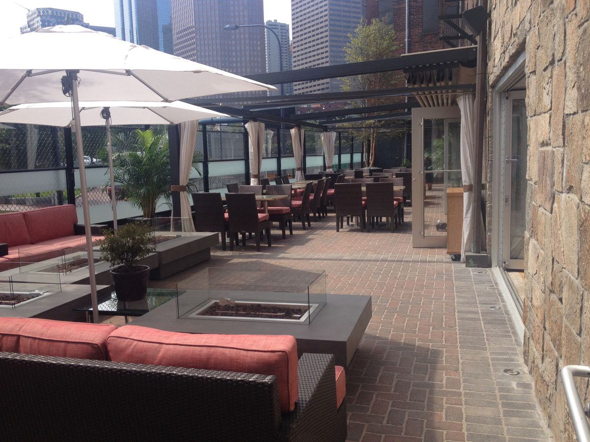 A patio in Boston's North End set up with umbrellas and fireplaces, and backdropped by the skyscrapers of the Financial District.