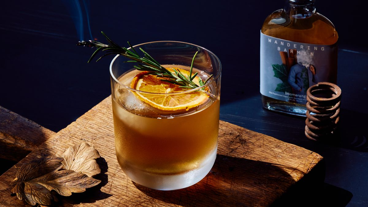 A cocktail glass topped with orange and a sprig of thyme sits besides a pre-batched cocktail.