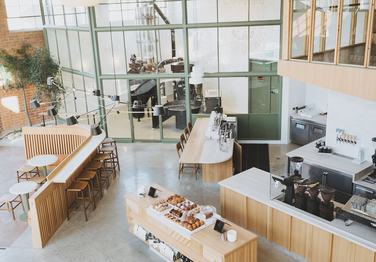 A bright, sunny cafe shown from above, with pastry case in the middle.