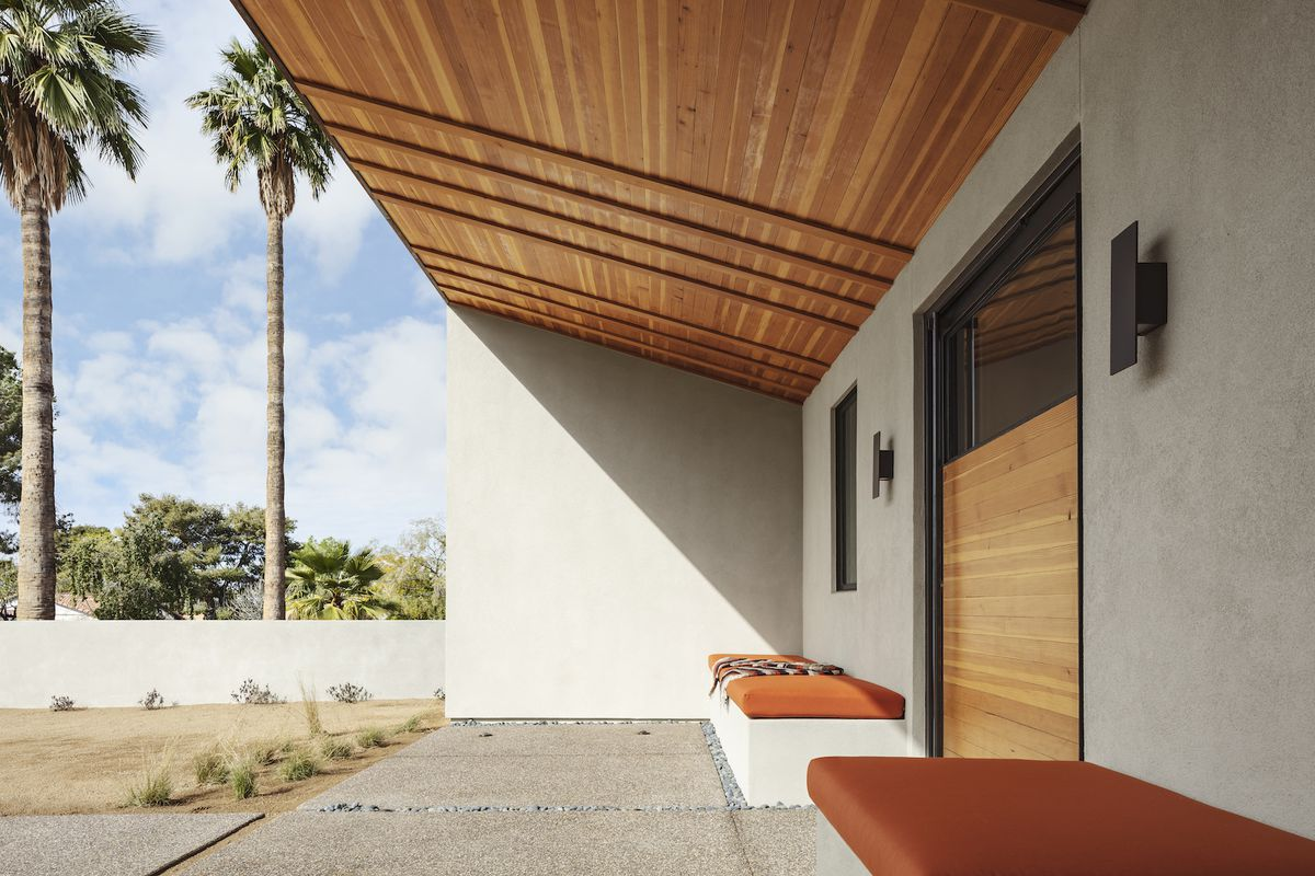 The exterior of a house. There are two benches with orange cushions against a concrete facade. The roof is wooden. In the distance are palm trees.
