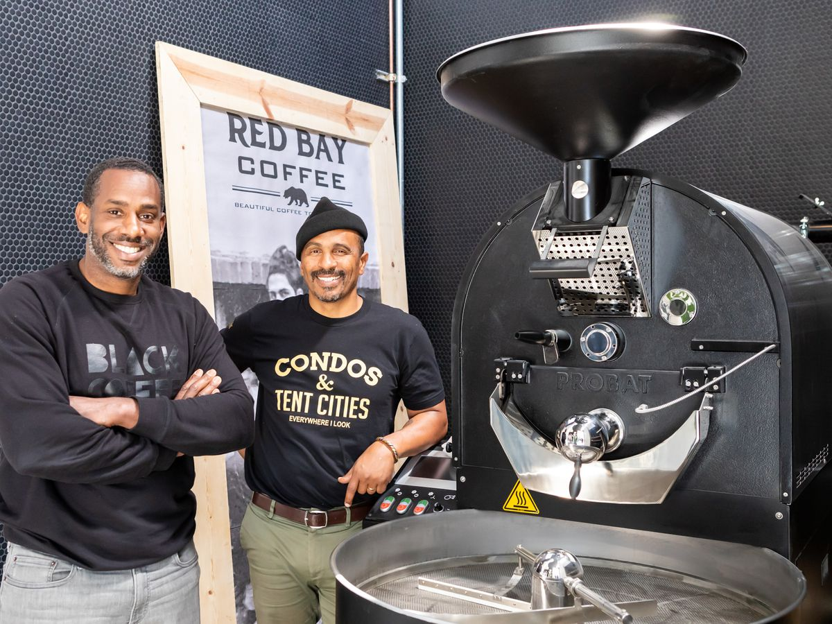 Two men stand beside a coffee roasting machine in front of a poster for Red Bay Coffee