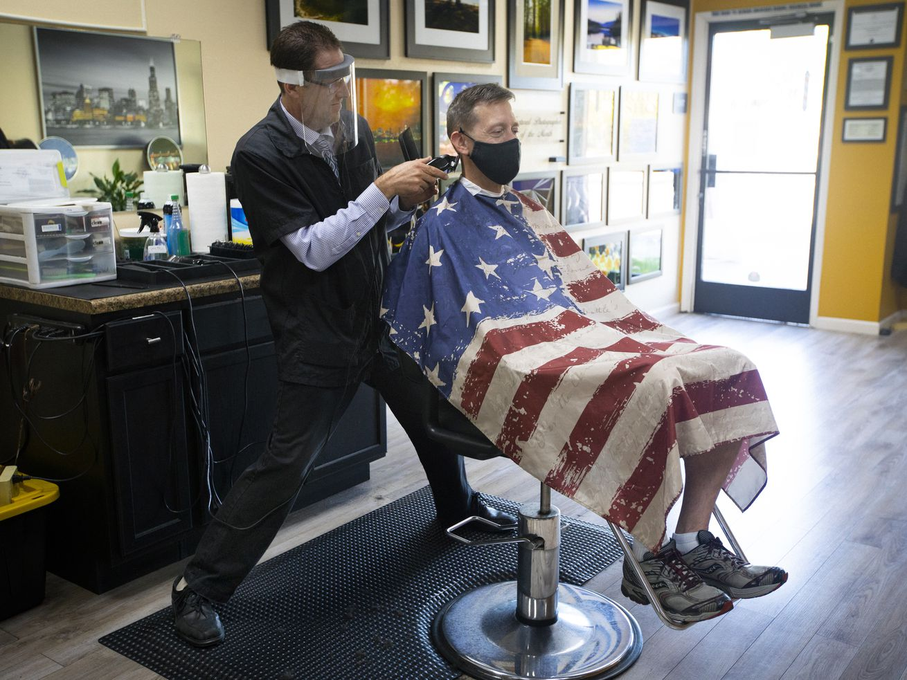 A man covered in a drape patterned like the American flag sits in a barbershop getting his hair cut by a barber.